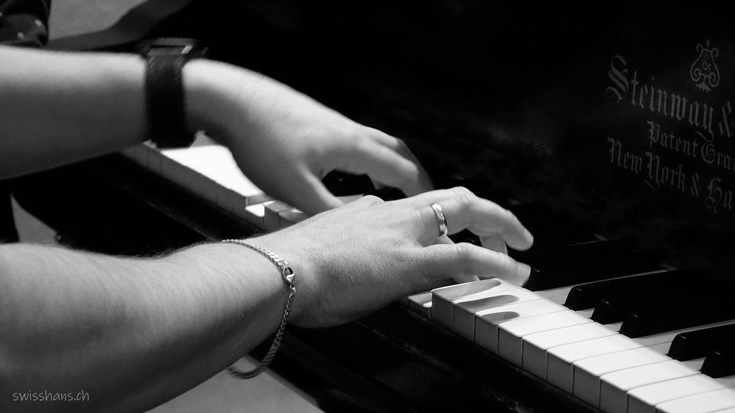 Flinke Hände eines jungen Pianospielers auf den Tasten des Klaviers