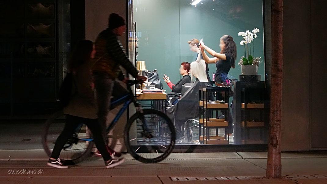 Nachtaufnahme mit Blick von der Strasse auf das Fenster eines Friseursalons mit Radfahrer im Vordergrund