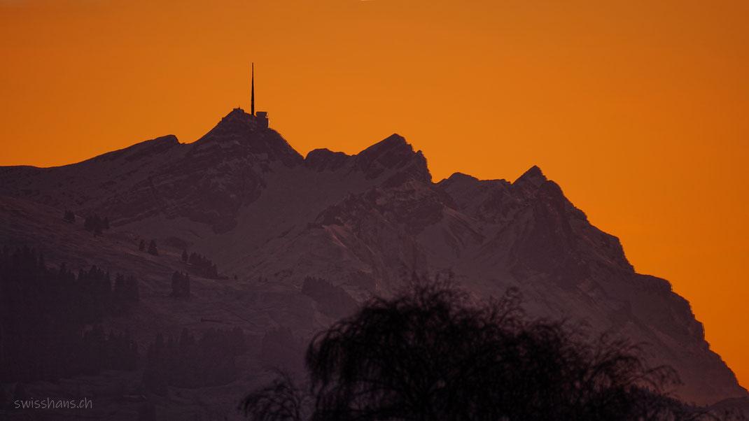 Säntis in bezaubernder Abendstimmung. Der verschneite Berg leuchtet im Abendrot.