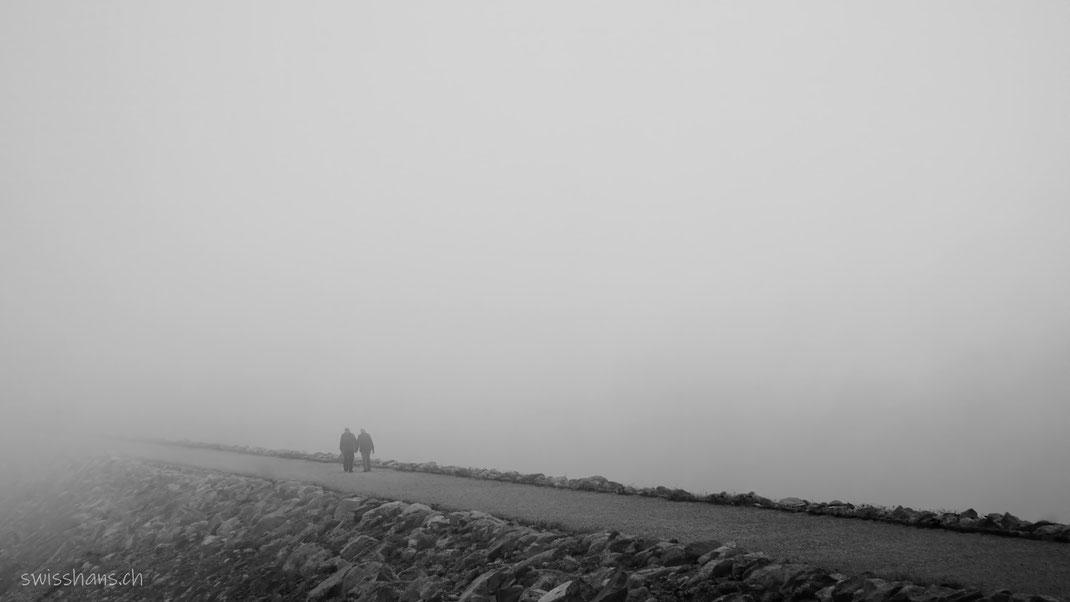 Zwei ältere Personen wandern auf einer Strasse in den Nebel hinein