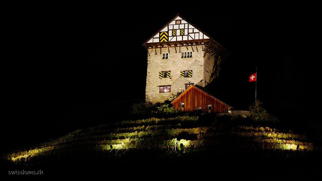 Die beleuchtete Burg Neu-Altstätten in der dunklen Nacht mit wehender Schweizerfahne.