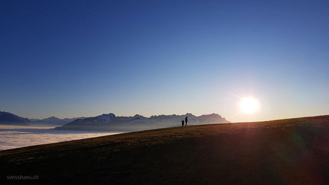 Blick vom Berg St. Anton zum Berg Säntis und dem Berg Hoher Kasten. Nebelmeer im Rheintal und zwei Personen auf der Anhöhe.