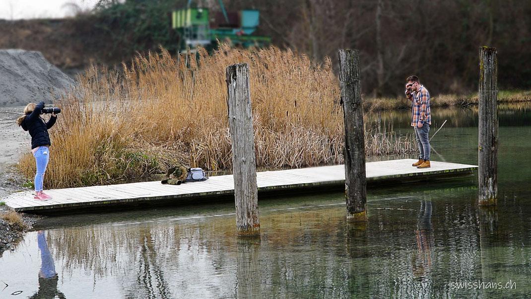 Eine Frau mit Kamera fotografiert einen jungen Mann auf einem Holzsteg beim Alten Rhein