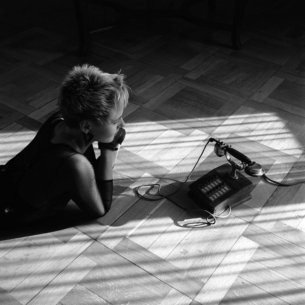 Portraitaufnahme von Model Ulla liegend mit historischem Telefon by Martin Boelt Portrait Photography