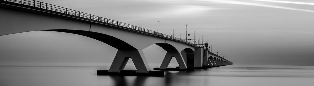 Zeelandbrücke in den Niederlanden mit eingeschalteten Laternen
