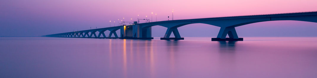 Zeelandbrücke (Zeelandbrug) in den Niederlanden kurz nach Sonnenuntergang mit eingeschalteter Beleuchtung