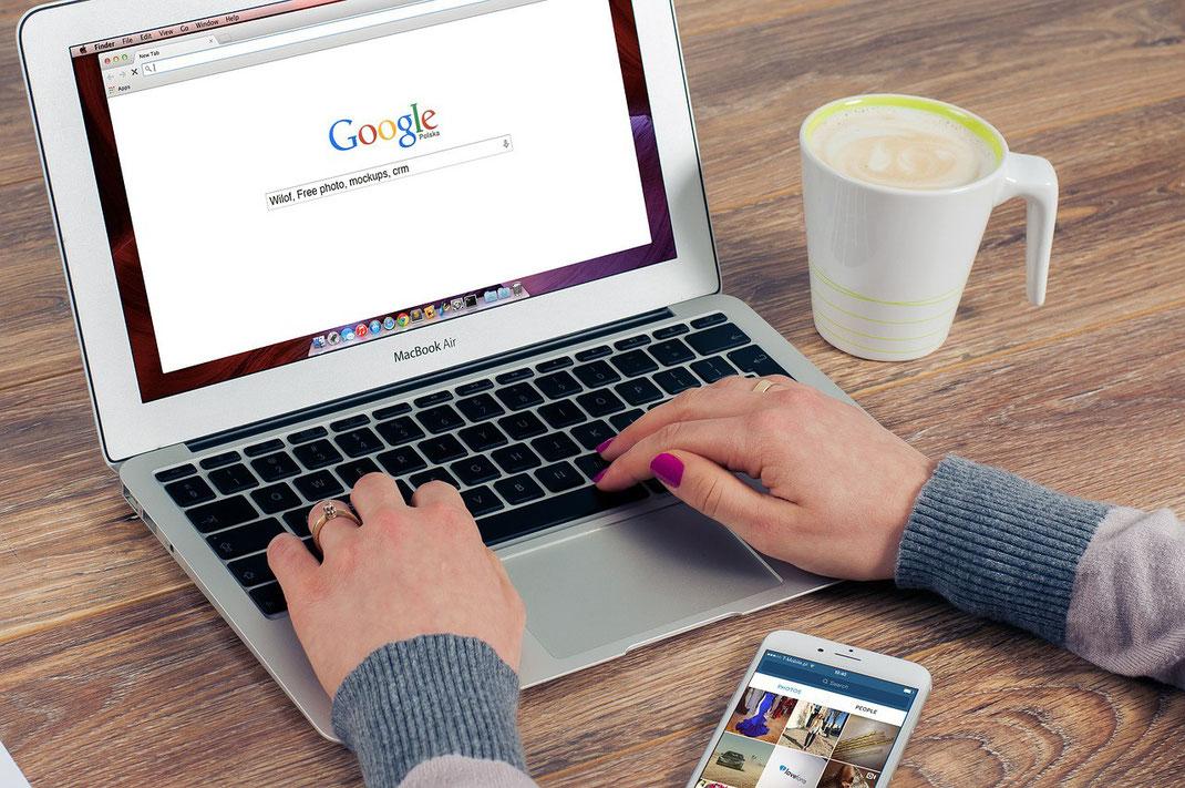 Frau tippt auf einem Laptop Suchbegriffe in einen Webbrowser