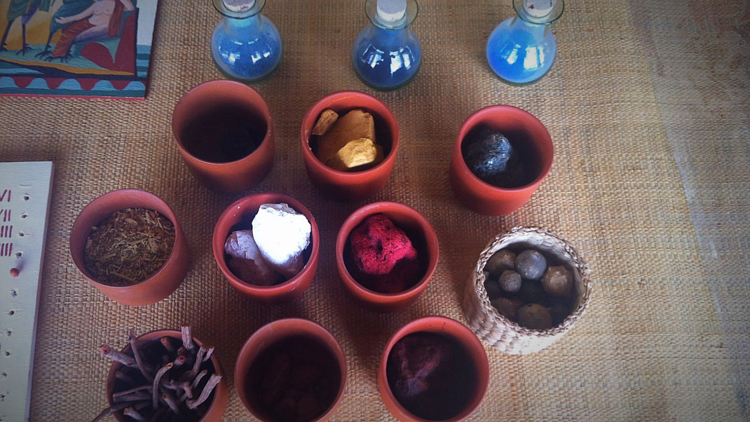 Up (in bottles, from the left): Azurite, indigo from wode, egyptian blue. First row (pots): Azurite, gold ocre, green earth. Middle row: Reseda, chalk, cinnabar, galls (basket). Lower row: Krapp roots, ruddle, red ocre.
