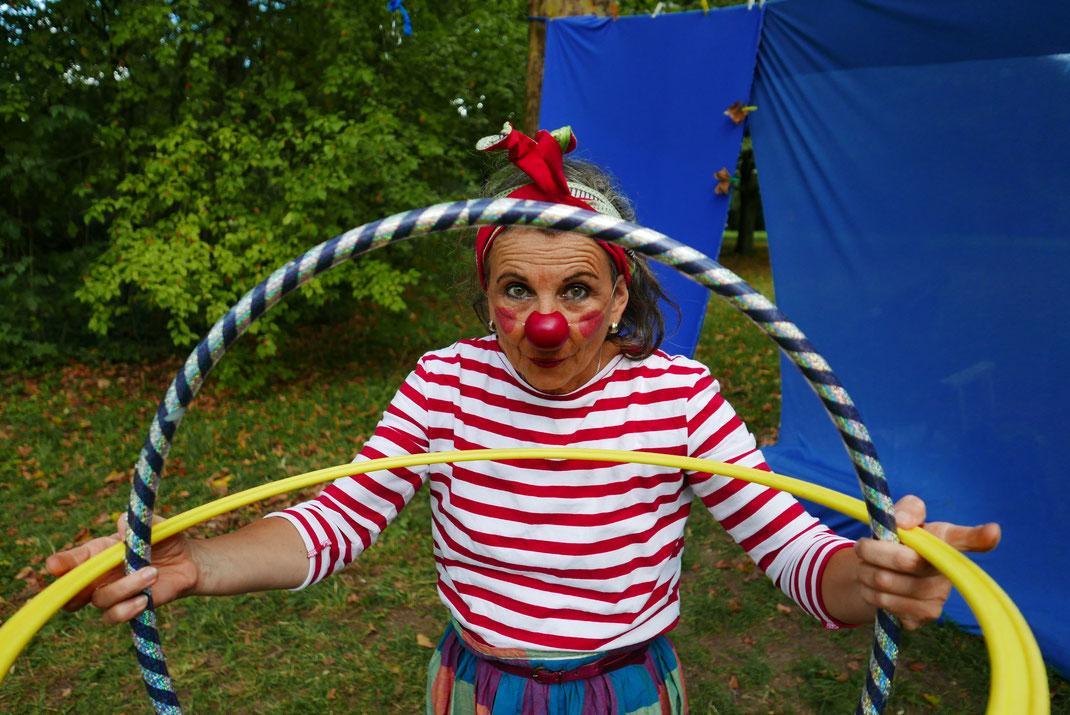 Firla, Poesie im Park, Wiesbaden 2019. Clownin mit gestreiftem Shirt hält 2 Reifen in der Hand und schaut durch.