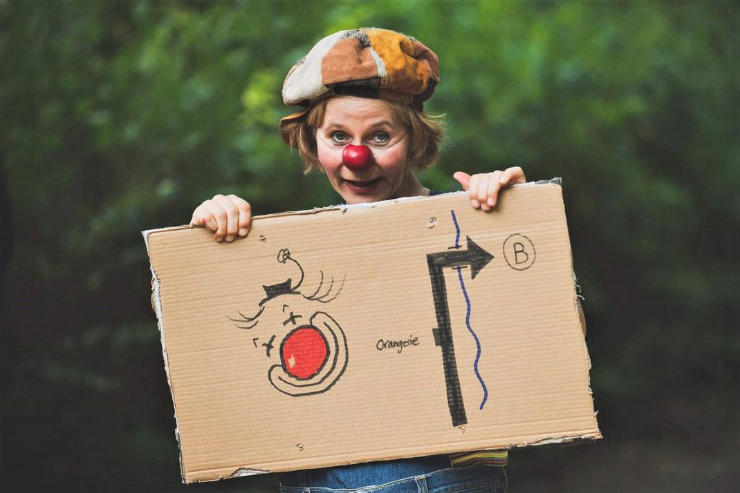 Clownin mit Kappe und roter Nase hält Pappschild vor sich mit Clown-Zeichnung und Zeichnung eines Weghinweises zur Spielstätte