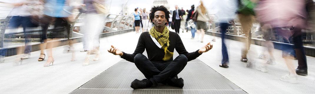 Entspannter Mann in Meditationshaltung genießt die Vorzüge der Achtsamkeit inmitten der Stresssituation einer vorbeieilenden Menschenmenge