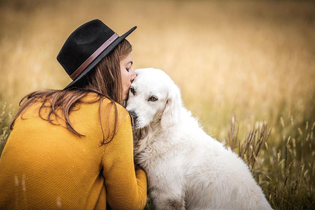 Mädchen mit langen Haaren und gelber Strickjacke sitzt in einer Blumenwiese mit Ihrem Golden Retriever und küsst sein Ohr fotografiert von der Hundefotografin Monkeyjolie im Prättigau