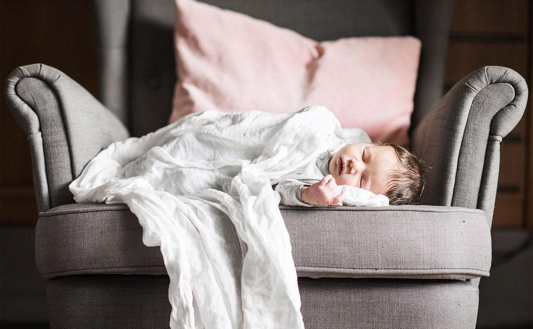 Baby liegt auf einem grauen Sofa eingewickelt in ein weisses Tuch fotografiert von der Familien Fotografin Monkeyjolie in Szene gesetzt