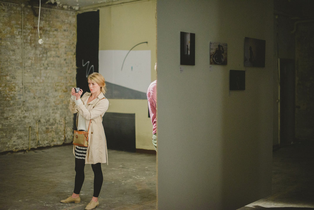 a blonde white woman takes pictures of the exhibition with her smartphone