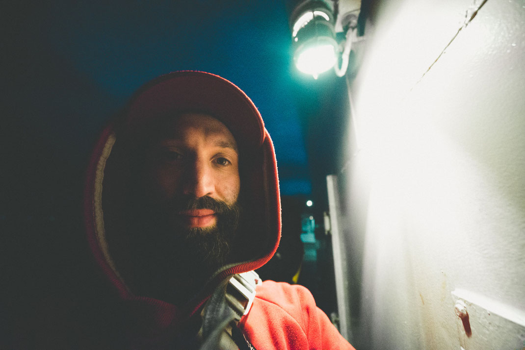 a bearded man with hoodie on a ferry deck looking into the camera