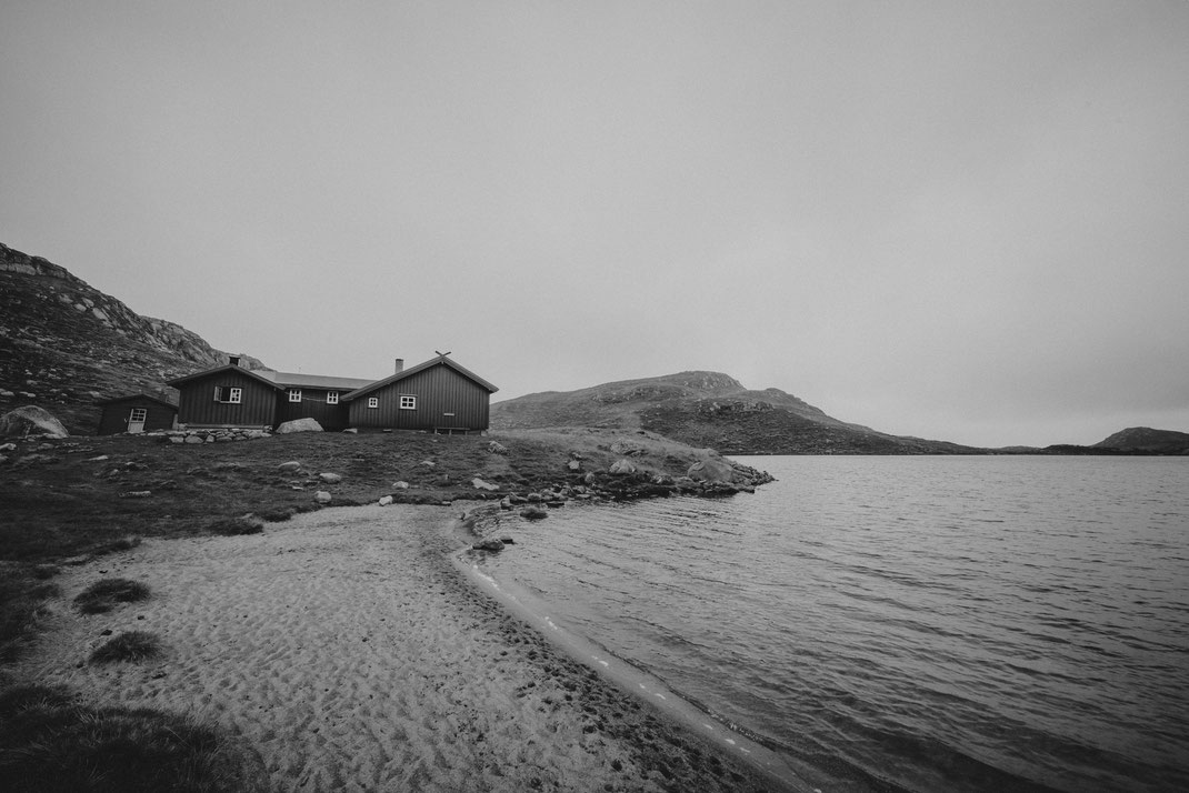 a black & white image of a cabin and a beach at a lake