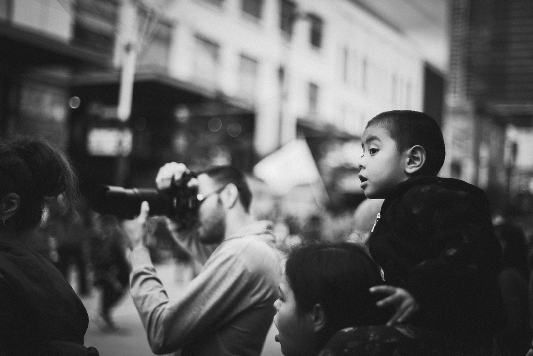 an asian boy looking excited at a Halloween parade on the shoulders of his mother
