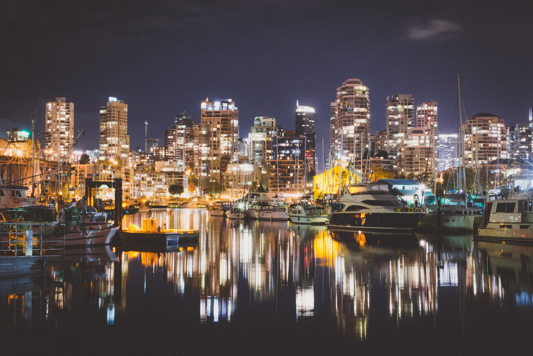 the city skyline of Vancouver at night near False Creek