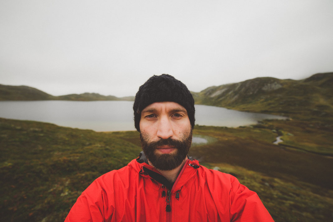 a portrait of a bearded man with red jacket in front of a lake in the highlands