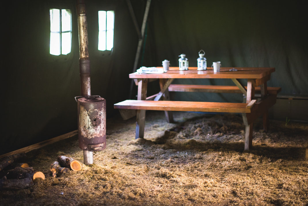 an old oven and a wooden bank in a military tent