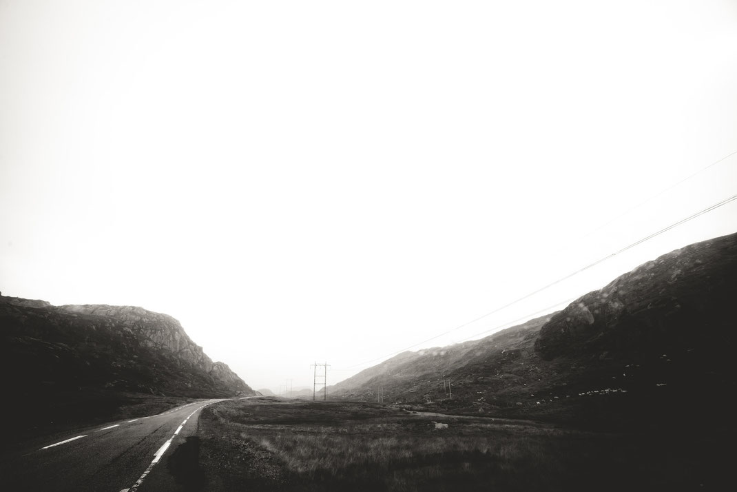 a black & white image of a road and electricity pylons in the rainy highlands