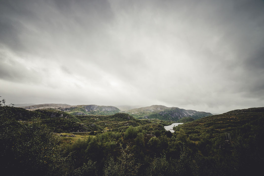 a cloudy landscape covered with trees and hills around a lake