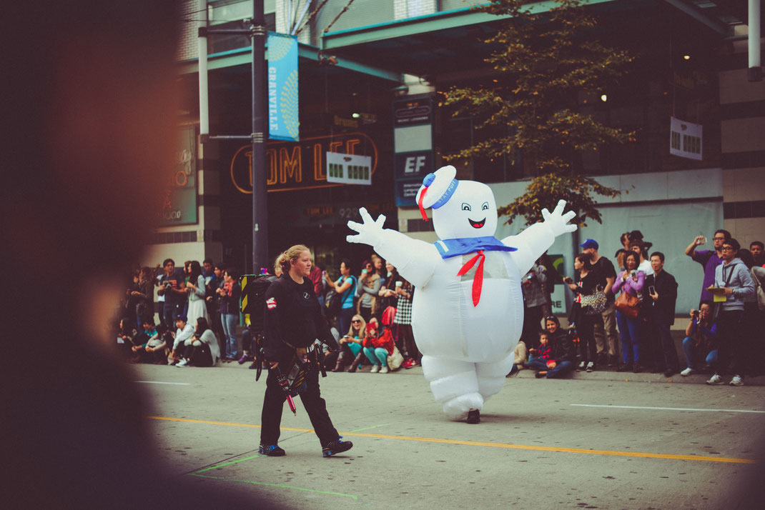 Marshmallow man and a member of the Ghostbusters walking on the Halloween parade