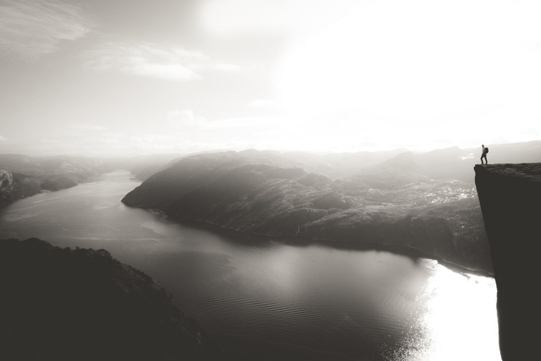 a black & white image of a person standing at the edge of a cliff looking over the fjord