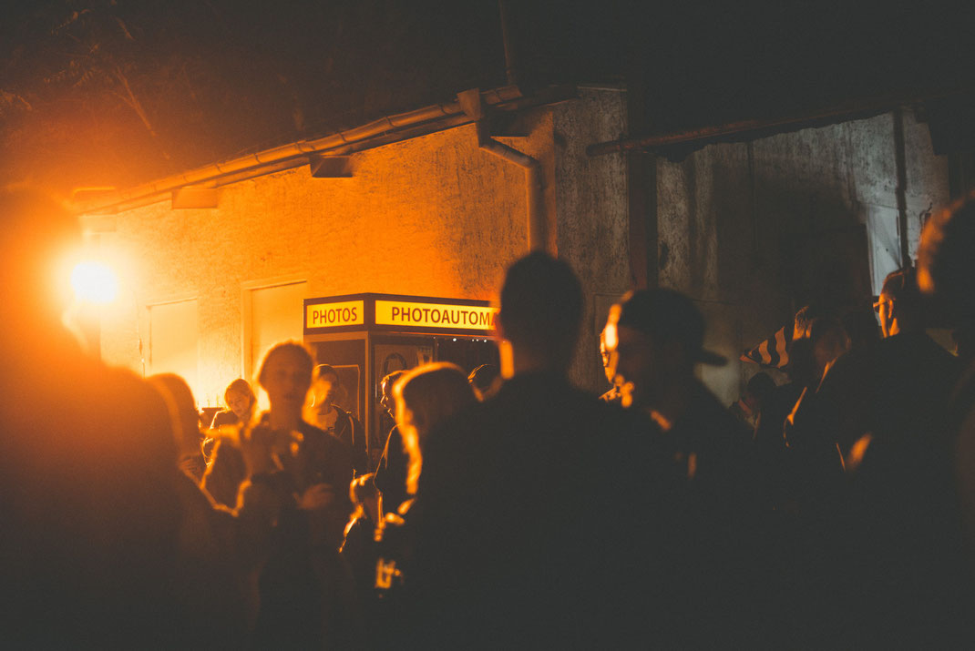 a photo booth standing in a crowd illuminated by backlight
