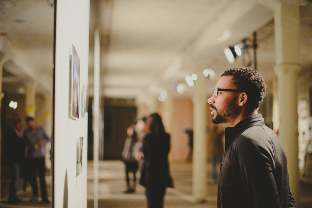 A black man looking at pictures at the exhibition