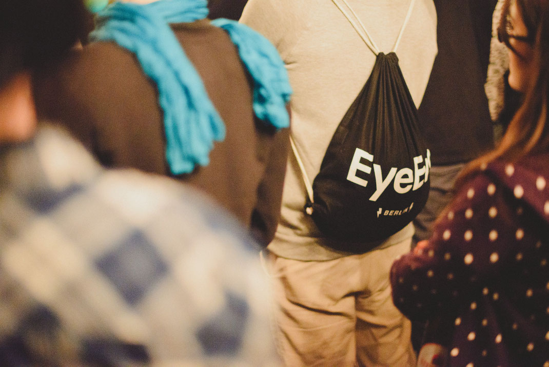 a man standing in the crowd with an eyeem bag