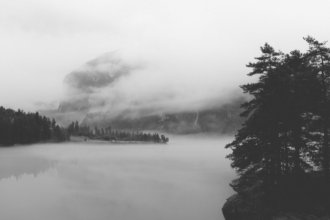 a black & white image of a misty lake