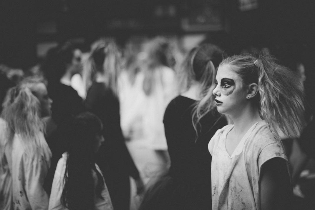 a creepy blonde girl walking at a Halloween parade