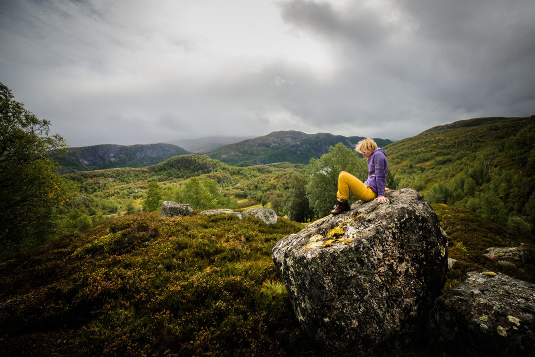 a blonde girl sitting thoughtful on a big rock on a hill