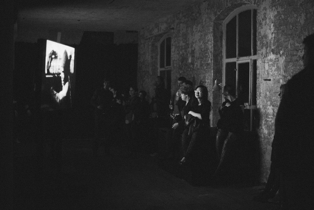 a black & white image of a group of people watching the contributions to the awards on a large monitor