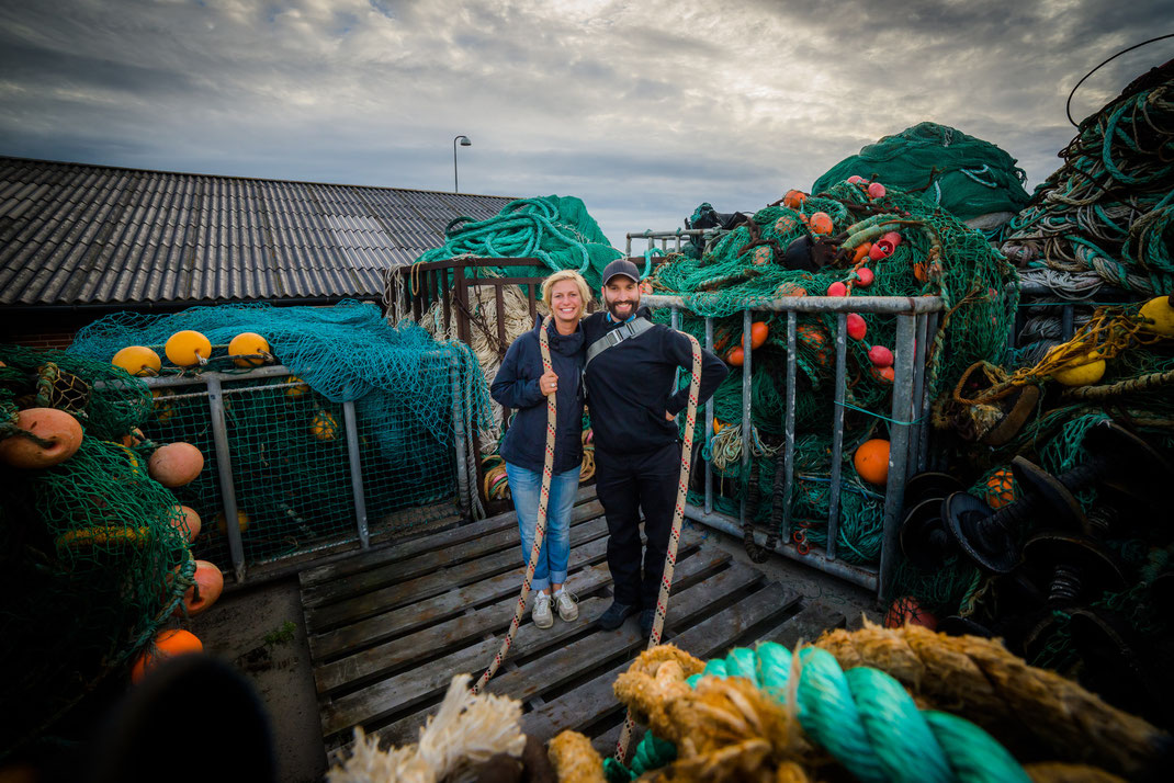 A blonde girl and a bearded man standing in the middle of fishermen's nets