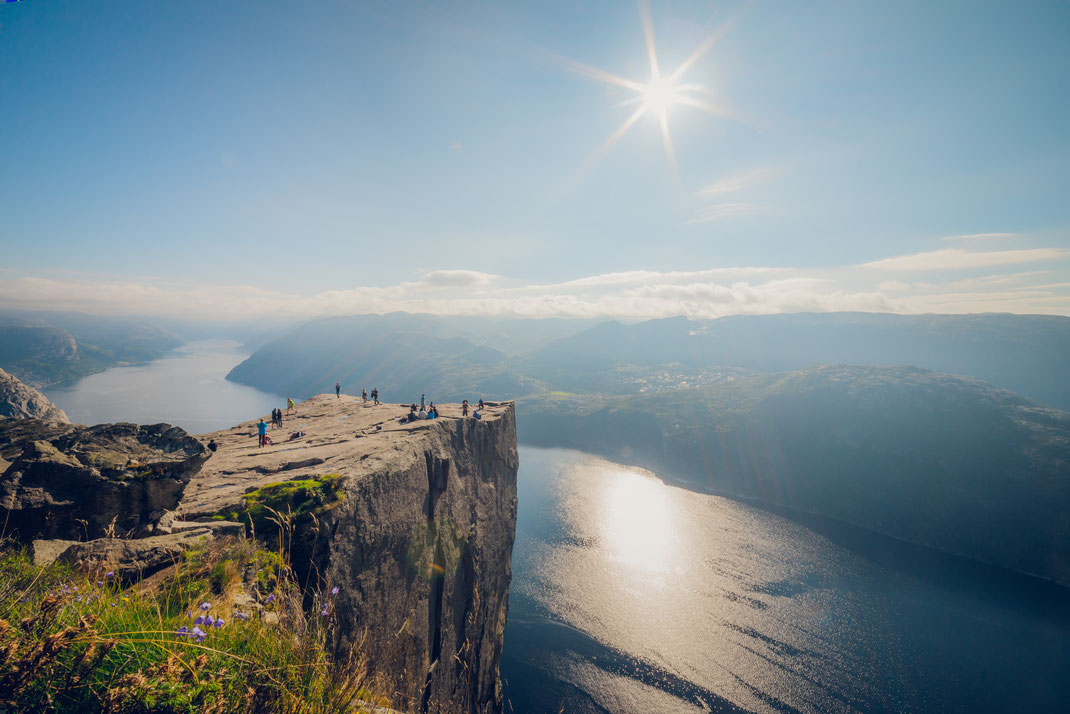 a couple of people enjoying a sunny day on the cliff of Preikestolen