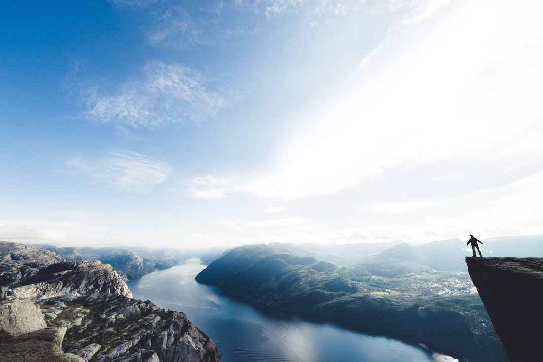 a person standing at the edge of a cliff looking over the fjord