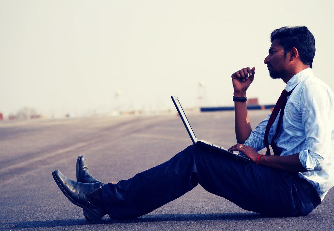 Mann im Businessoutfit sitzt am Boden , auf dem Schoß ein Laptop.
