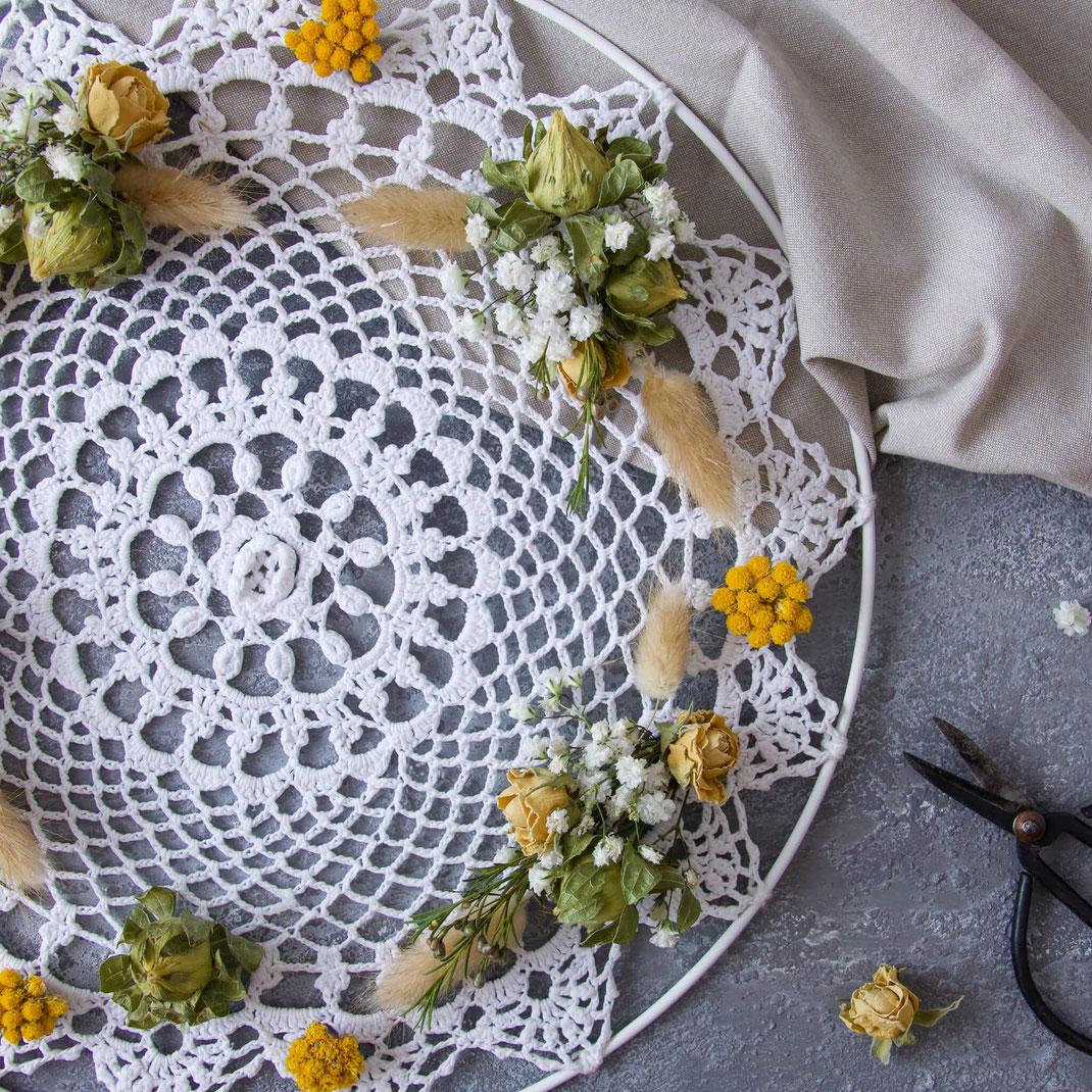 Weisses Häkeldeckchen mit getrockneten gelben und weissen Blumen dekoriert