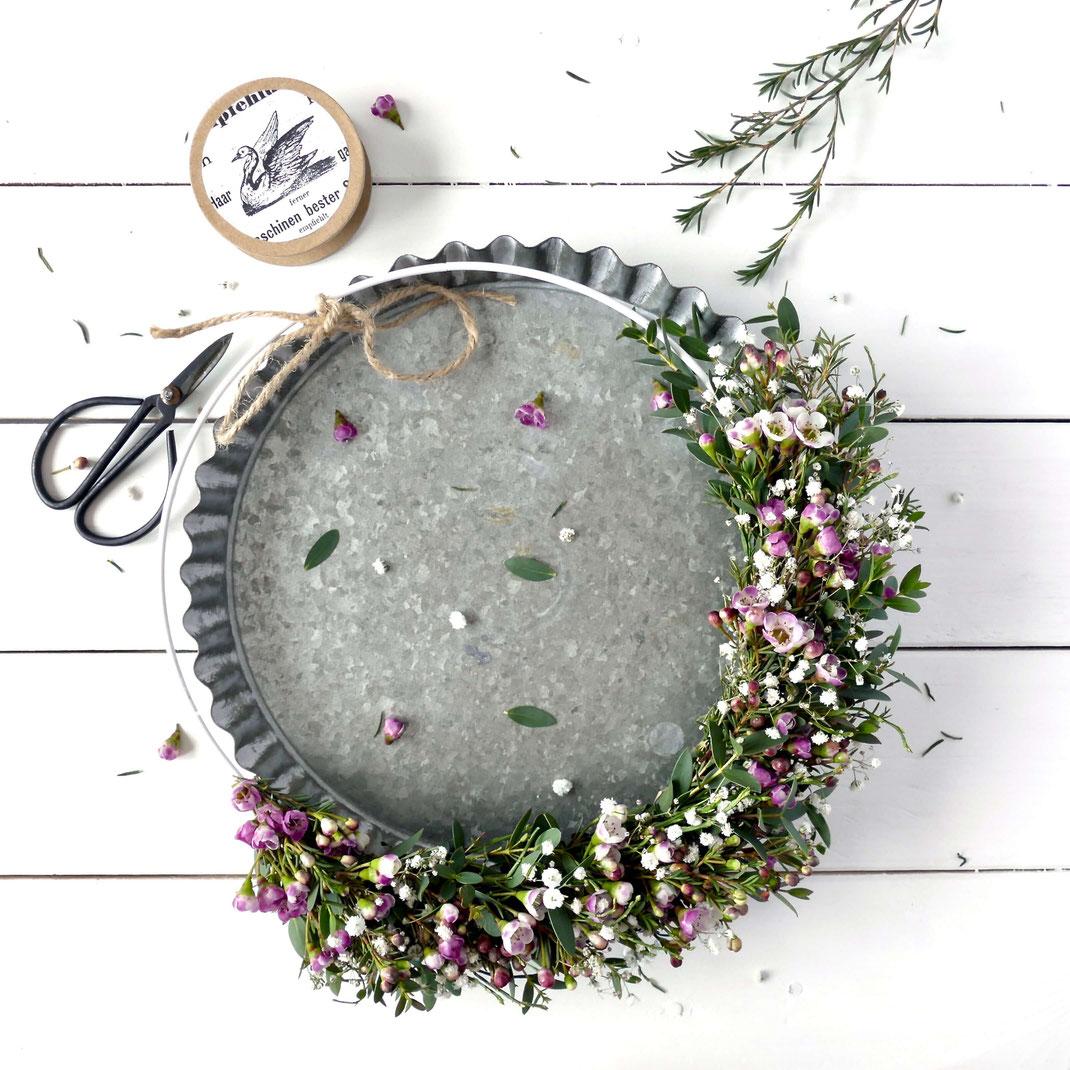 Bunte Blumen an Metallring gebunden auf einer Kuchenform