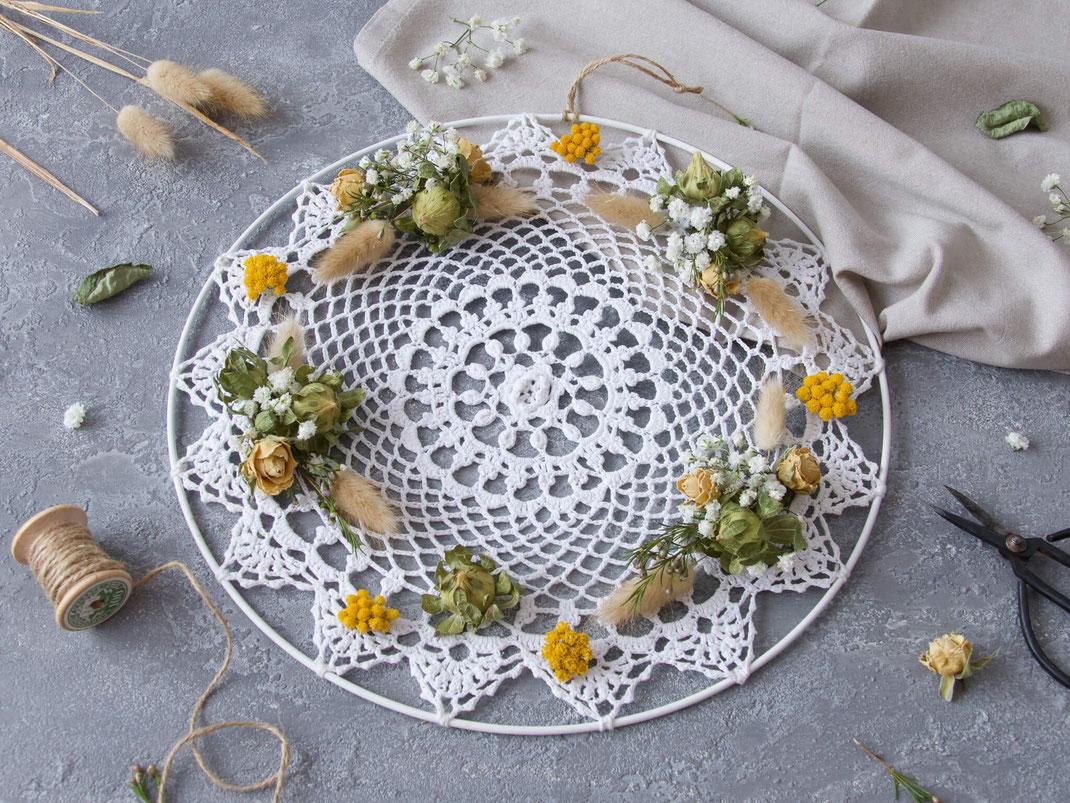 Weisses Spitzendeckchen im Metallring dekoriert mit getrockneten Blumen