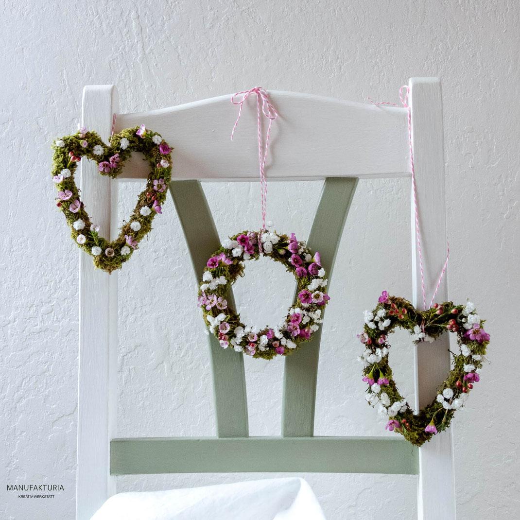 Kleine Kränze rundund und herzförmig mit Wachsblumen und Schleierkraut an einem Stuhl aufgehängt