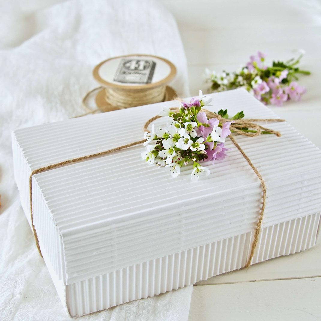 Weisse Geschenk Schachtel mit Schleife und einem kleinen Blumensträusschen