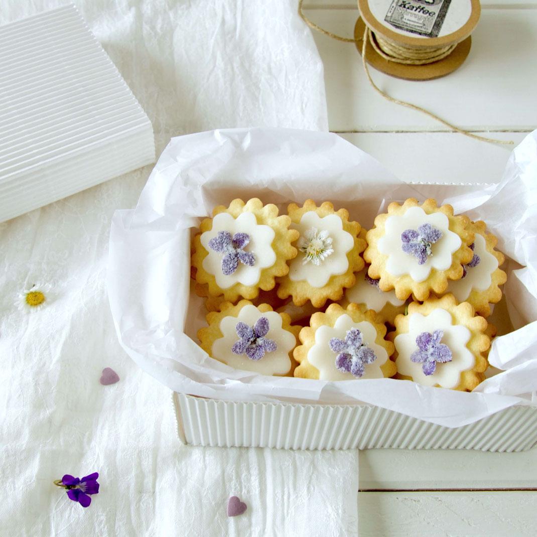 Mürbeteig Kekse mit zuckrigen Veilchen in der selber gemachten Geschenkbox