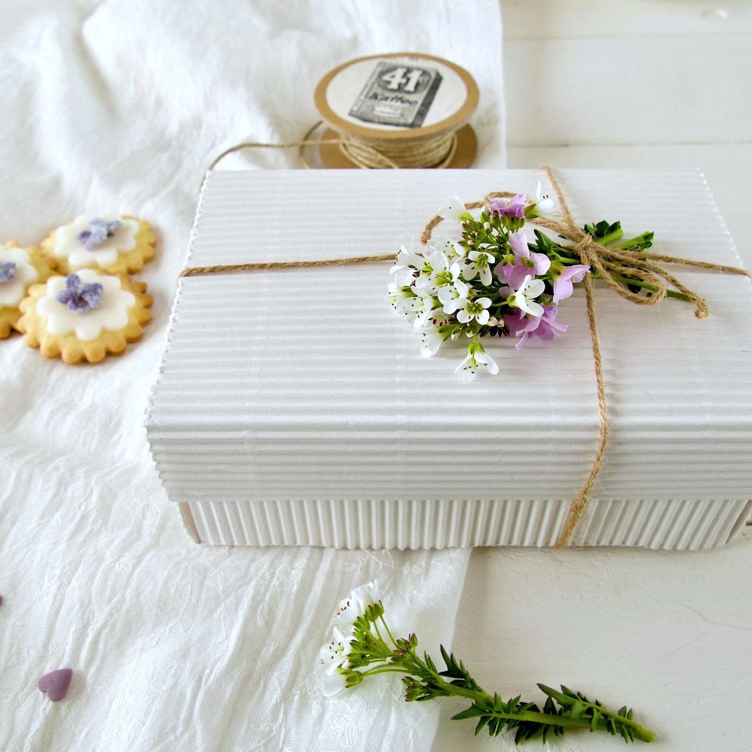 Weisse Geschenkbox aus Wellpappe mit Blumen verziert