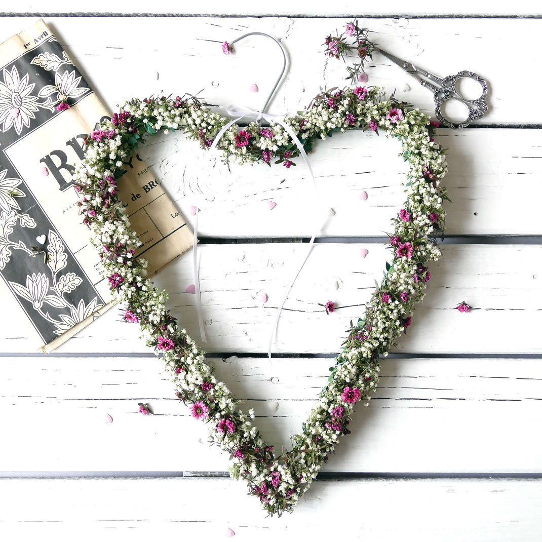 Kranz in Herzform mit verschiedenen Blumen und gebogenem Haken zum Aufhängen
