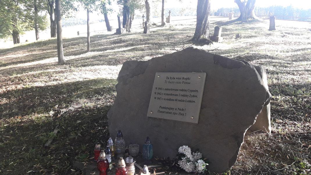 """Übersetzung der Gedenktafel: """"Hier stand das Dorf Ropki. 1941 wurde ein Zigeuner, 1942 zwei Juden ermordet, 1947 wurden 60 lemkische Familien vertrieben. Wir vergessen nie!"""""""