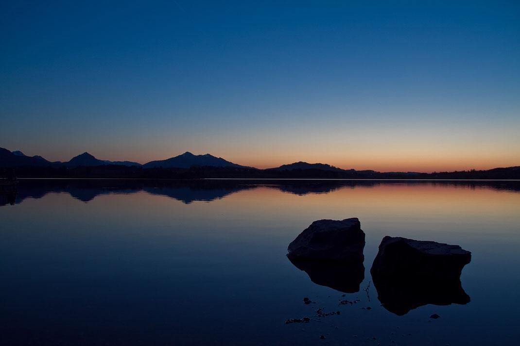 allgäu, süddeutschland, seeufer, hopfensee, sonnenuntergang, dämmerung, blaue stunde, felsen, berge, steine, spiegelung