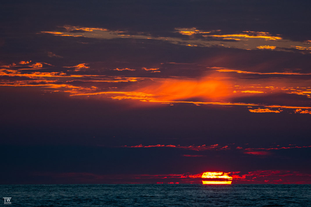 Zum Sonnenuntergang blitzte der Sonnenball nochmal durch die Wolkendecke hervor (B2619)